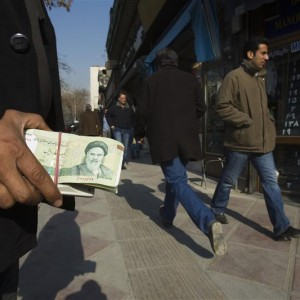 File photo of a money changer holding Iranian rial banknotes as he waits for customers in Tehran's business district